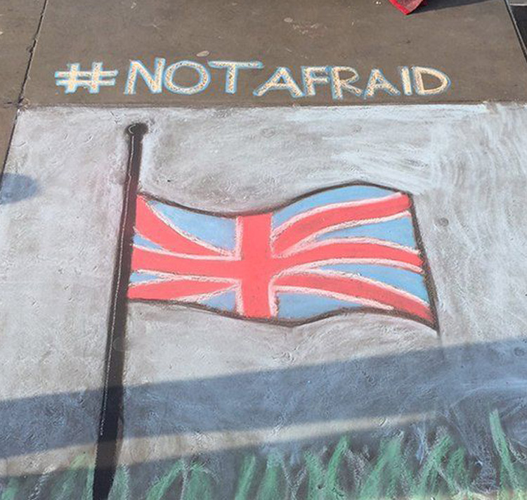 People sign messages of hope on street art after London attack