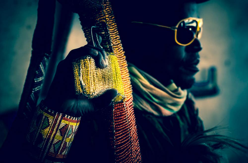 Close up of beaded colorful AK47 with man carrying it wearing yellow sunglasses