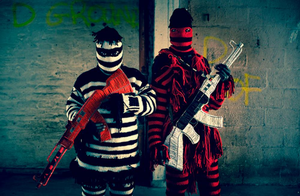 2 men with striped outfits carrying colorful AK 47s