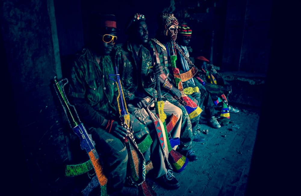 4 men in Camouflage sitting carrying AK 47s